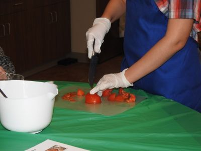 A student cuts up tomato for salsa